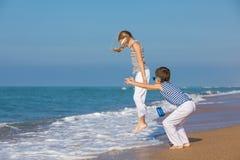 2 счастливых дет играя на пляже на времени дня Стоковое Фото