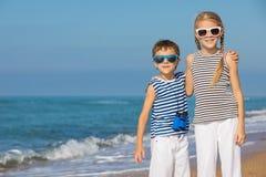 2 счастливых дет играя на пляже на времени дня Стоковые Изображения RF
