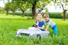 2 счастливых дет играя с большим старым автомобилем игрушки в лете садовничают, внешний Стоковое Изображение