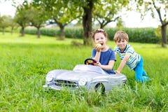 2 счастливых дет играя с большим старым автомобилем игрушки в лете садовничают, внешний Стоковое Фото