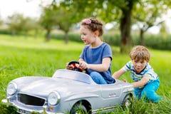 2 счастливых дет играя с большим старым автомобилем игрушки в лете садовничают, внешний Стоковые Изображения RF