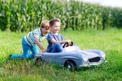 2 счастливых дет играя с большим старым автомобилем игрушки в лете садовничают, внешний Стоковое Изображение RF