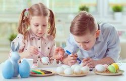 2 счастливых дет имея потеху во время картины eggs для пасхи внутри Стоковое Фото