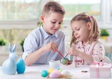 2 счастливых дет имея потеху во время картины eggs для пасхи внутри Стоковые Изображения