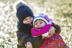 2 счастливых дет мальчик и девушка играя outdoors в солнечной зиме Стоковая Фотография