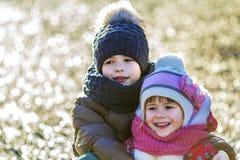2 счастливых дет мальчик и девушка outdoors в солнечном зимнем дне Стоковая Фотография RF