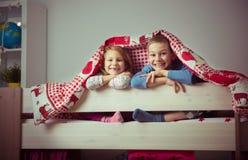 2 счастливых дет отпрыска имея потеху в двухъярусной кровати Стоковые Изображения