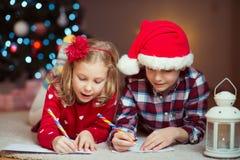 2 счастливых дет писать письмо к Санта Клаусу дома около Ne Стоковые Изображения