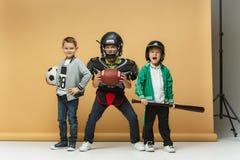 3 счастливых дет показывают различный спорт Концепция моды студии Концепция эмоций Стоковые Изображения