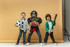 3 счастливых дет показывают различный спорт Концепция моды студии Концепция эмоций Стоковые Фотографии RF