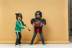 2 счастливых дет показывают различный спорт Концепция моды студии Концепция эмоций Стоковая Фотография