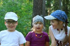 3 счастливых дет сидят, усмехаются и говорятся Стоковая Фотография