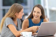 2 счастливых друз говоря около на линии содержании Стоковые Фото