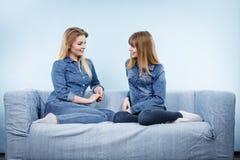 2 счастливых друз женщин нося говорить обмундирования джинсов Стоковые Изображения RF