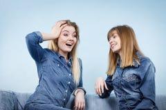 2 счастливых друз женщин нося говорить обмундирования джинсов Стоковая Фотография