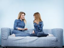 2 счастливых друз женщин нося говорить обмундирования джинсов Стоковые Фотографии RF