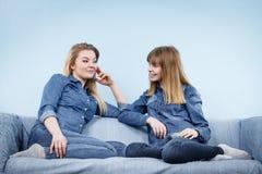 2 счастливых друз женщин нося говорить обмундирования джинсов Стоковое Фото
