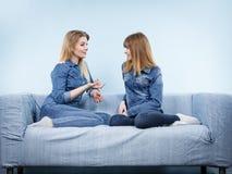 2 счастливых друз женщин нося говорить обмундирования джинсов Стоковое фото RF
