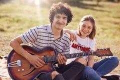 2 счастливых друз имеют радостное выражение, gentle улыбки на сторонах, recreat во время временени внешнего, гитара игры и поют п Стоковое Фото