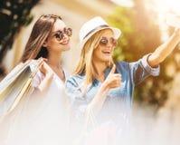 2 счастливых друз принимая Selfie пока ходящ по магазинам Стоковая Фотография
