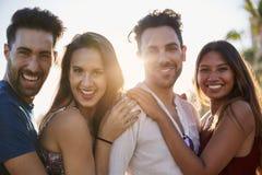 4 счастливых друз стоя совместно снаружи в солнечном свете Стоковые Фотографии RF