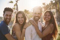 4 счастливых друз стоя совместно снаружи в усмехаться Стоковое фото RF