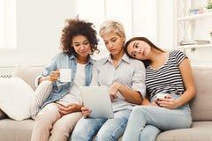 3 счастливых женских друз используя таблетку и выпивающ кофе Стоковое фото RF