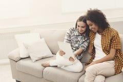 2 счастливых женских друз используя таблетку Стоковая Фотография RF
