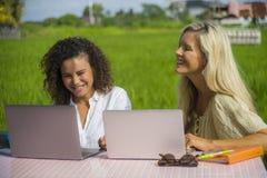 2 счастливых женских друз работая outdoors на красивом интернет-кафе с женщиной портативного компьютера кавказской и афро смешанн Стоковое Изображение