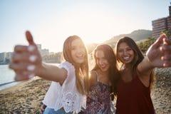 3 счастливых женских друз стоя на руках повышения пляжа Стоковое Изображение RF