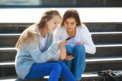 2 счастливых женских подростка говоря совместно в улице Стоковая Фотография
