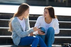 2 счастливых женских подростка говоря совместно в улице Стоковое фото RF