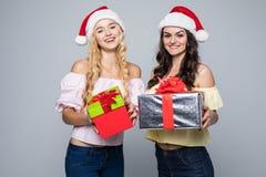 2 счастливых женщины в шляпах santa при подарочные коробки стоя на белой предпосылке Стоковая Фотография RF
