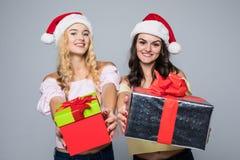 2 счастливых женщины в шляпах santa при подарочные коробки стоя на белой предпосылке Стоковое Изображение RF