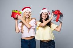 2 счастливых женщины в шляпах santa при подарочные коробки стоя на белой предпосылке Стоковое Изображение