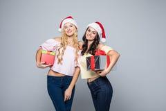 2 счастливых женщины в шляпах santa при подарочные коробки стоя на белой предпосылке Стоковое фото RF