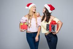2 счастливых женщины в шляпах santa при подарочные коробки стоя на белой предпосылке Стоковые Фотографии RF
