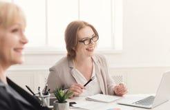 2 счастливых женщины работая совместно в современном офисе Стоковые Фотографии RF