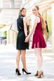 2 счастливых женщины смотря камеру пока носящ duri бумажных сумок Стоковые Фото