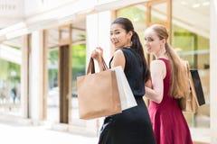 2 счастливых женщины смотря камеру пока носящ duri бумажных сумок Стоковые Изображения