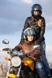 2 счастливых женщины управляя совместно на одном велосипеде, пассажире стоят за сиденьем водителя Стоковое фото RF