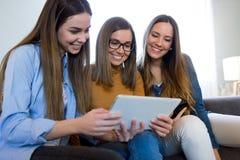 3 счастливых красивых женщины используя цифровую таблетку дома Стоковое Фото