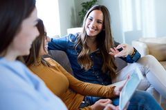 3 счастливых красивых женщины используя цифровую таблетку дома Стоковая Фотография RF