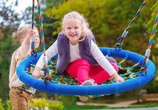 2 счастливых маленьких дет имея потеху на качании Стоковая Фотография