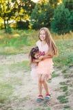 2 счастливых маленькой девочки имея потеху и обнимая на солнечном лете Стоковые Изображения RF