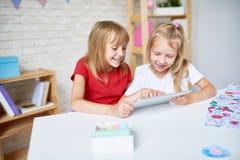 2 счастливых маленькой девочки используя таблетку цифров стоковая фотография rf
