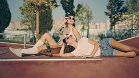 2 счастливых маленькой девочки при longboard имея потеху совместно пока сидящ на парке конька Мода лета, отдых и видеоматериал