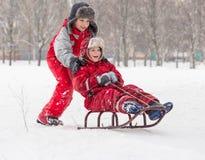 2 счастливых мальчика ехать на скольжении на снежном городе паркуют Стоковая Фотография