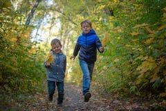 2 счастливых мальчика, который побежали через парк осени стоковая фотография rf