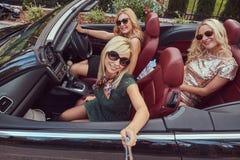 3 счастливых модных женских друз принимают фото selfie в роскошном автомобиле cabriolet, во время их каникул отключения Стоковые Изображения